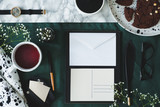 Envelope, postcard, tea, pen, quill, glasses, watch and cake on a desk. Top view - 219788872