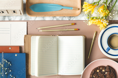 Notebook, pencils, flowers and pen in the shape of feather on a creative desk. Top view
