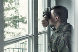 Depressed and sad soldier in green uniform with trauma after war standing near the window - 219789043