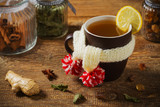 Cup with scarf with hot tea. - 219789423