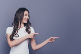 Portrait of magnificent nice pretty lovely gorgeous adorable stylish cheerful curly-haired girl in casual white t-shirt, pointing with two hands, looking aside, isolated over grey background