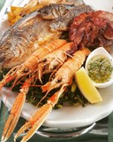 Grilled seafood served on plate with sauce - 219792822