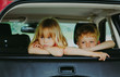 little girl and boy waiting in car bored sad tired