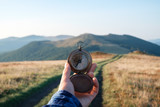 Man with compass in hand on mountains road. Travel concept. Landscape photography - 219798891