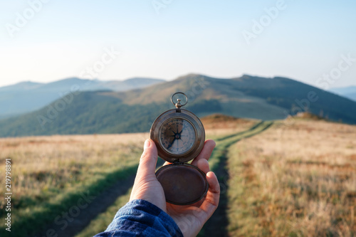 Leinwanddruck Bild Man with compass in hand on mountains road. Travel concept. Landscape photography