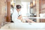 Frau entfernt Haar durch Rasur des Beines im Bad eines Hotels - 219800420