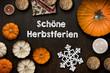 """Holzhintergrund mit Aufschrift """"Schöne Herbstferien"""" mit herbstlicher Dekoration"""