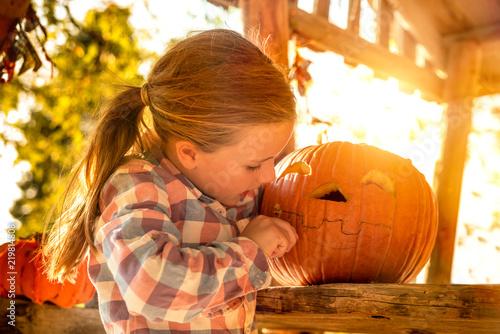 Leinwandbild Motiv Little girl carving Halloween pumpkin outdoors.