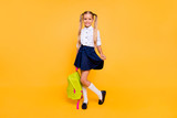 Full length, legs, body, size portrait of sweet, gorgeous, adorable, small blonde girl stand isolated on shine yellow background