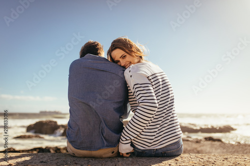 Foto Murales Couple sitting on a sea wall together