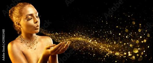 Złoty makijaż - modelka dmuchająca złotym pyłem