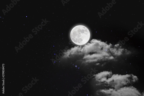 Romantic night. Full moon  over cloudscape with wood background.