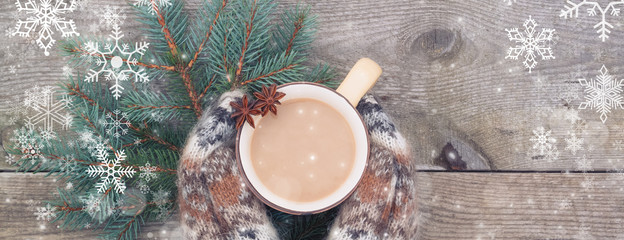 Woman hands in white and brown woolen gloves holding a coffee mug on snow vintage tone, banner © Ekaterina Senyutina