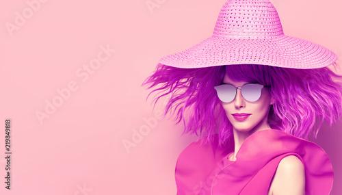 Młoda piękna kobieta w różowej letniej sukience, Strona fioletowy fryzurę. Fashion Studio Portrait Glamour Lady. Zabawny model dziewczyna w stylowy kapelusz, modne okulary przeciwsłoneczne. Kreatywna sztuka