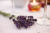 Bunch of fresh lavender and a burning candle - 219851431