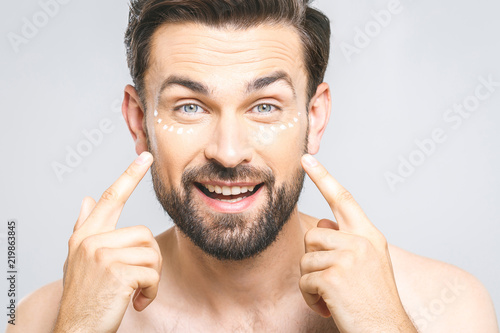 Skin Care Handsome Young Shirtless Man Lying Cream At His Face And Looking Himself
