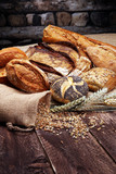 Different kinds of bread and bread rolls on wooden table - 219873083