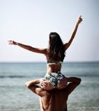 Happy cheerful couple have fun girl sitting  on boyfriend shoulders. Romantic vacation, honeymoon love - 219876097