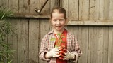 Handheld shot of cute little girl wearing gloves standing against rustic wooden wall and holding potted seedling while smiling and posing for camera - 219888621
