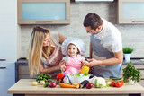 A happy family prepares food from vegetables in the kitchen. - 219909853