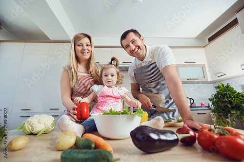 A happy family prepares food from vegetables in the kitchen.