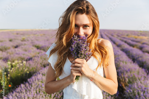 Leinwanddruck Bild Photo of happy young woman in dress holding bouquet with flowers, while walking outdoor through lavender field in summer