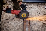 Close up of a strong  man welder in brown uniform,  welders leathers, grinder metal an angle grinder  at the construction site, orange sparks fly to the sides - 219915697