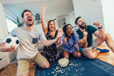 Happy friends or football fans watching soccer on tv and celebrating victory at home.Friendship, sports and entertainment concept. - 219918089