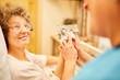 Leinwandbild Motiv Pflegekraft zeigt Frau mit Demenz ein Foto