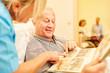 Leinwanddruck Bild - Senior Mann mit Demenz betrachtet Fotos
