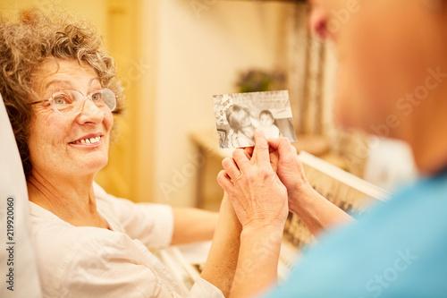 Leinwanddruck Bild Pflegekraft zeigt Frau mit Demenz ein Foto