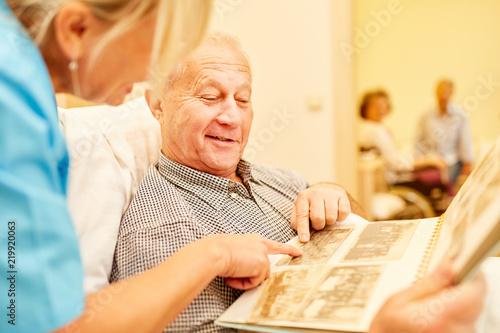 Leinwanddruck Bild Senior Mann mit Demenz betrachtet Fotos
