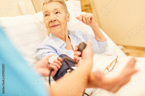 Leinwanddruck Bild Kontrolle des Blutdrucks bei Senior Frau
