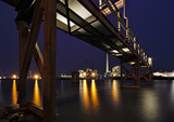 Bremen, Germany - Brightly lit harbor at night with rusty steel jetty above, yellow lights reflecting in the water and various industrial plants in the distance - 219932432