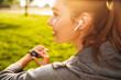 Leinwandbild Motiv Portrait of beautiful sporty woman 20s in sportswear using smartwatch and wireless earbud, while resting in green park