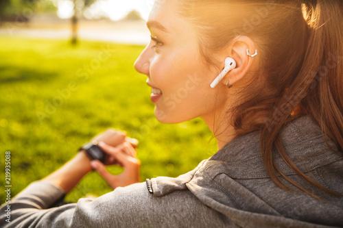 Leinwanddruck Bild Portrait of beautiful sporty woman 20s in sportswear using smartwatch and wireless earbud, while resting in green park