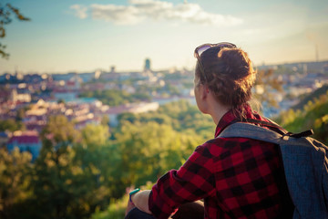 Young traveler woman tourist looking at a European city at sunset from a height, travel atmosphere, Vilnius, Lithuania