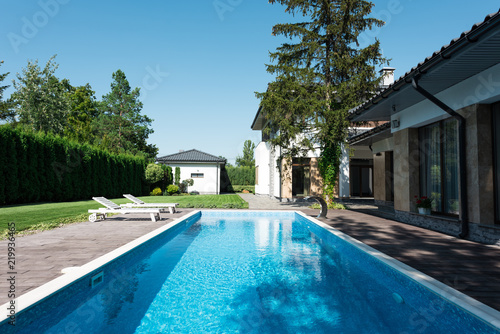 widok na dom, ogród i basen z leżakami do relaksu