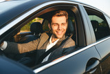 Front view of smiling bussinesman in suit driving - 219941235