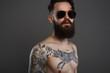 Bearded Man in sunglasses, naked tattoed Boy