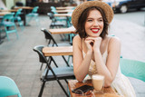 Smiling woman in dress and straw hat drinking coffee - 219951078