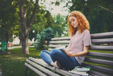 Young redhead woman with a notebook on the bench in the park - 219952823