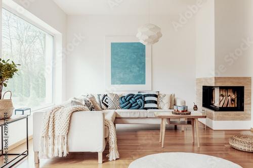 Turkusowa niebieska poduszka z węzłem na beżowej kanapie narożnej i abstrakcyjnym plakatem na białej ścianie we wnętrzu nowoczesnego salonu