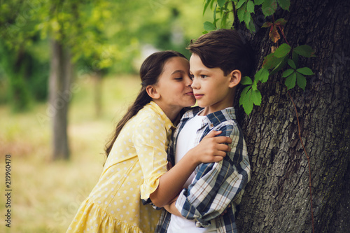 Beautiful Girl Kissing Young Man On Cheek Girl Leaning On Little
