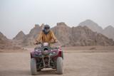 Portrait of a man on an ATV. Quad bikes safari in desert near Sharm El Sheikh, Egypt - 219973604