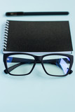Notebook with pen and and glasses on a blue background. - 219975231