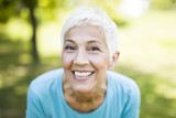 Portrait of a smiling sporty senior woman in a park - 219977885