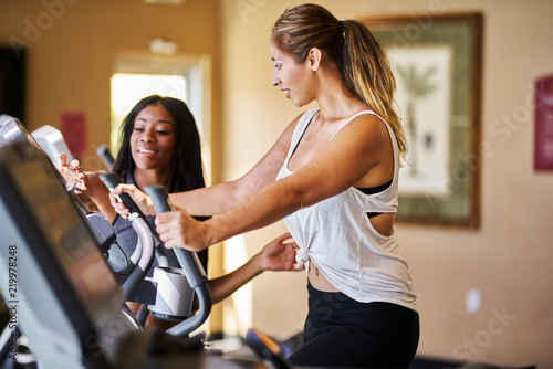 Wall mural personal trainer helping woman use treadmill in gym