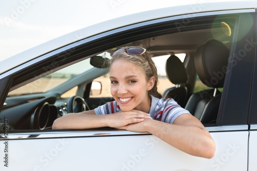 Leinwandbild Motiv Portrait of Smiling Young Woman in her Car