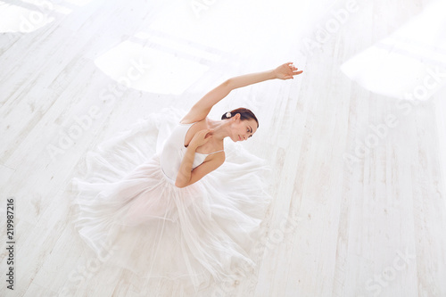 A ballerina in white clothes in a white light studio. - 219987216